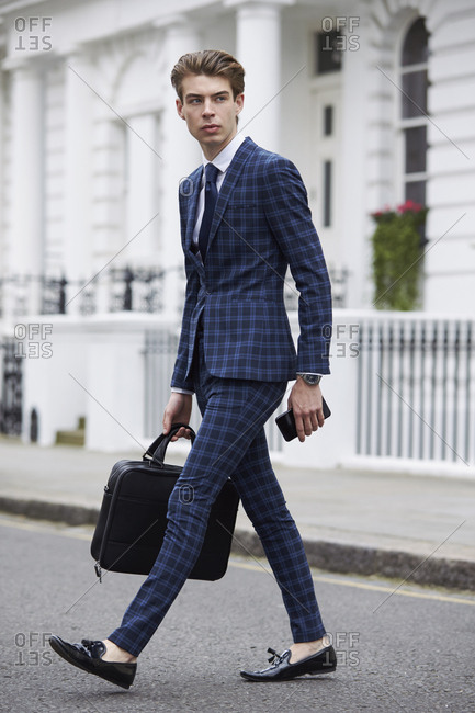 Young man in blue checked suit walking across the road