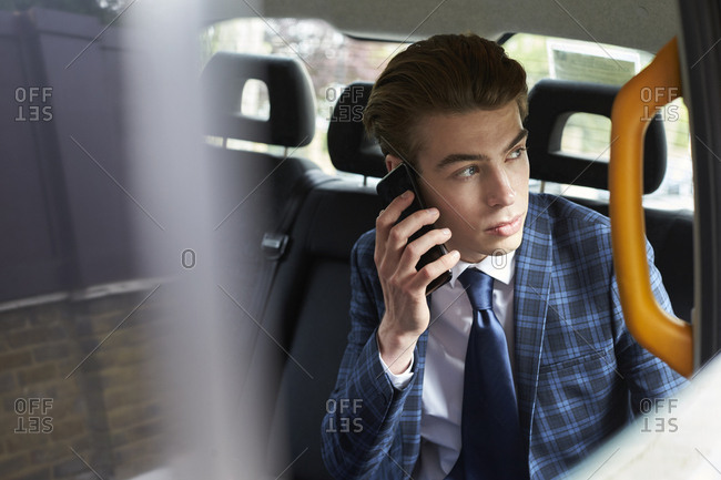 Young businessman on phone in taxi looking out of window