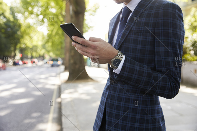 Businessman standing in street using smartphone, mid section