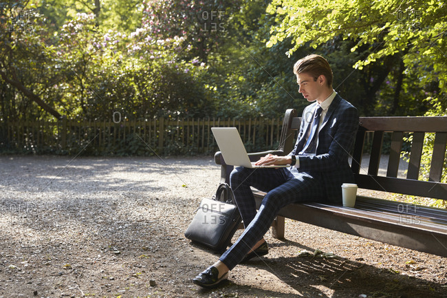 Young businessman using laptop on park bench