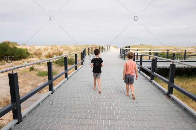 Brothers walking together on pathway leading to beach