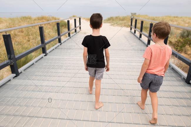 Two boys walking together on boardwalk toward beach