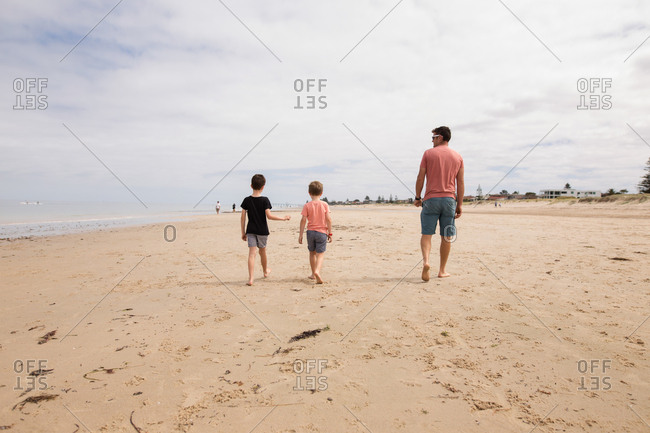 Father and sons walking together on sandy beach