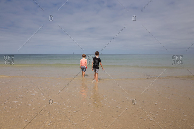 Two boys wading in calm water on the beach