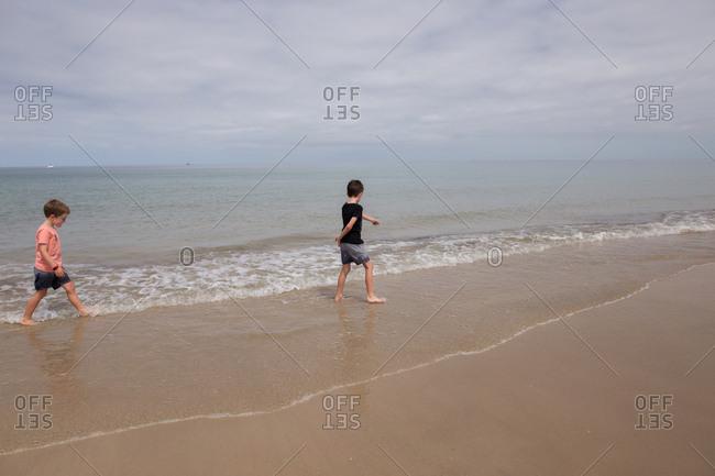 Two boys walking through waves on sandy beach