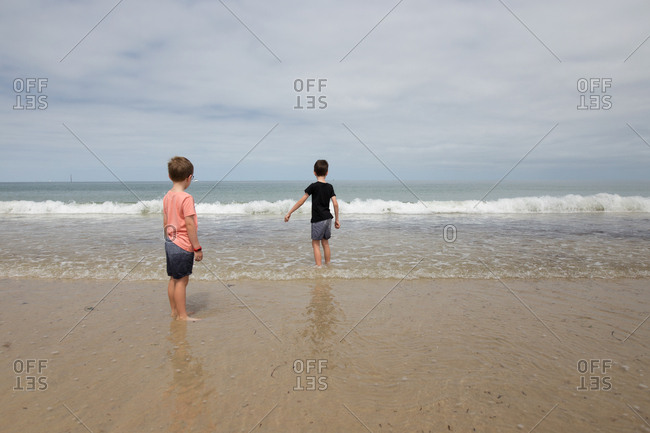 Two boys wading in waves on beach