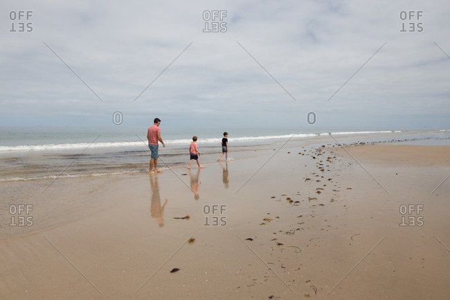 Father and sons wading through water on sandy beach