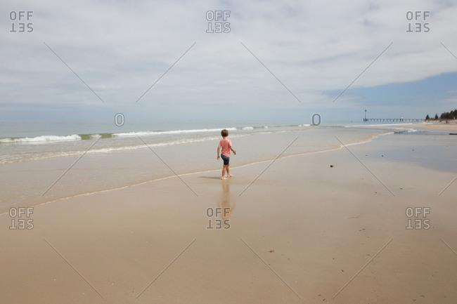 Boy walking alone on the beach