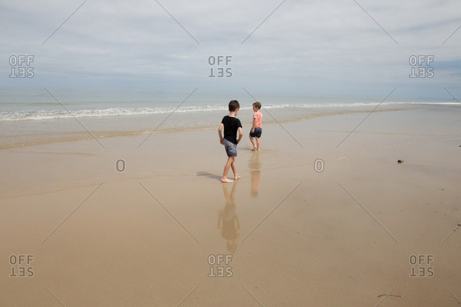 Two boys walking on wet sand at the beach