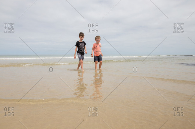 Two boys wading in shallow water on beach