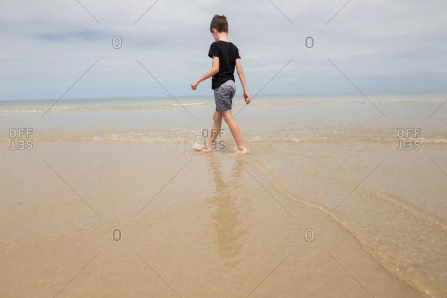 Boy wading through water on beach