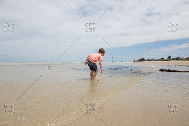 Boy looking at water coming in from ocean wave