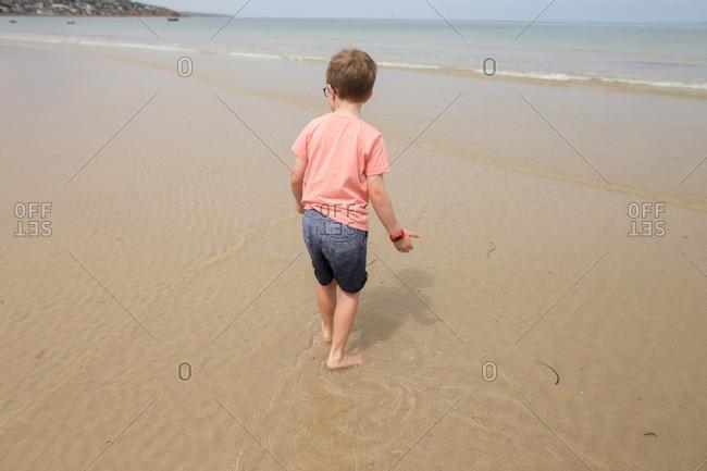 Boy standing in water coming in from ocean wave