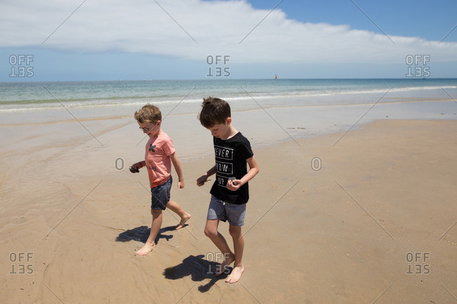 Two boys holding objects collected while walking on beach