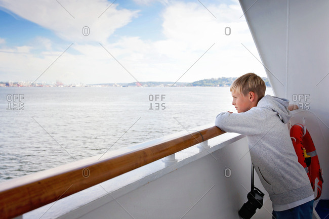 Boy looking at ocean from cruise ship