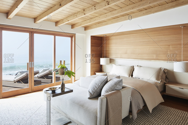 Malibu, California - March 15, 2017: Interior of a master bedroom with patio overlooking water designed by Chad Eisner