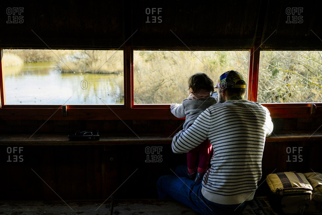 Dad holding toddler daughter on his knees while bird watching