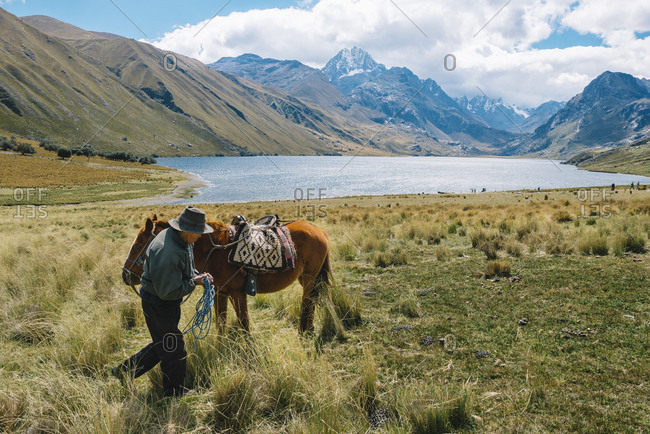 Huaraz, Peru - September 21, 2016: Man with horse in mountainous landscape in Peruvian Andes