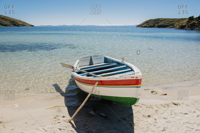 Colorful row boat pulled up onto the sand on Isla Del Sol, Lake Titicaca, Bolivia
