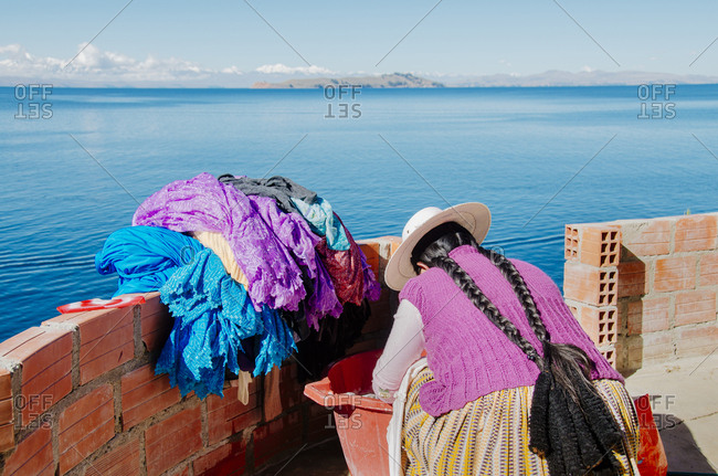 Local woman doing laundry overlooking Lake Titicaca, Bolivia
