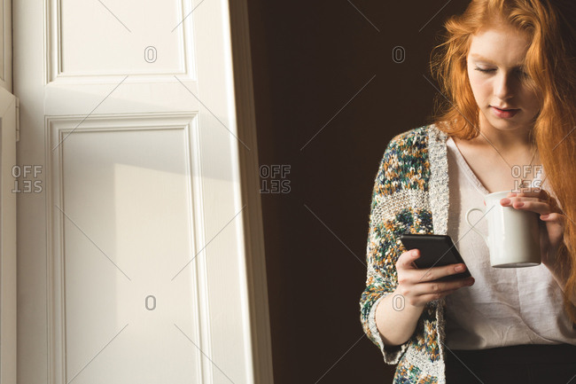Woman having coffee while using mobile phone at home