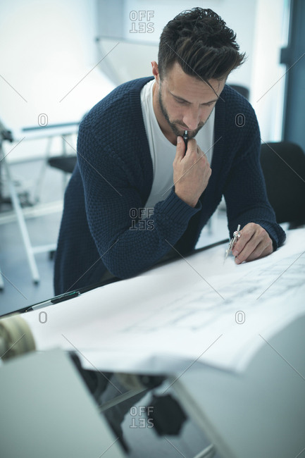 Executive working on blueprint in office