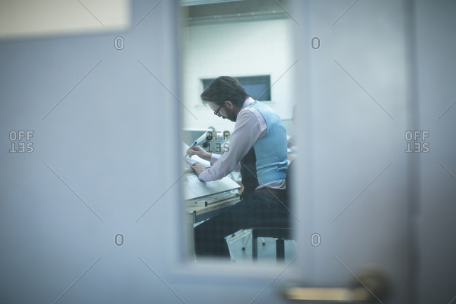 Executive working over drafting table in office