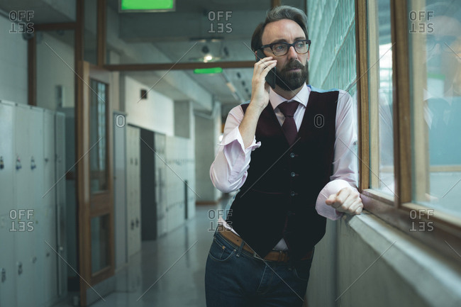 Executive talking on mobile phone in office corridor