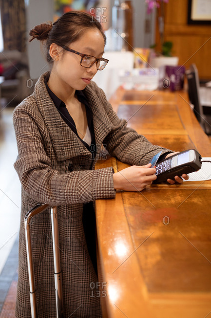Woman executive swiping his card on payment terminal machine at reception area