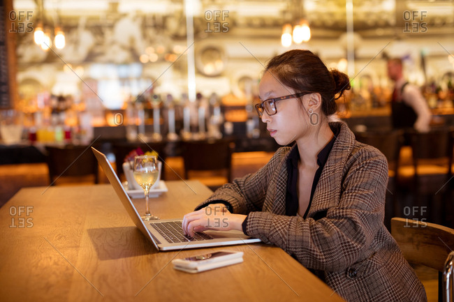 Female executive using laptop at table in hotel