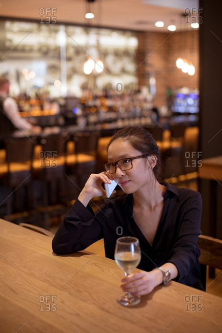 Woman talking on mobile pone while having wine in hotel