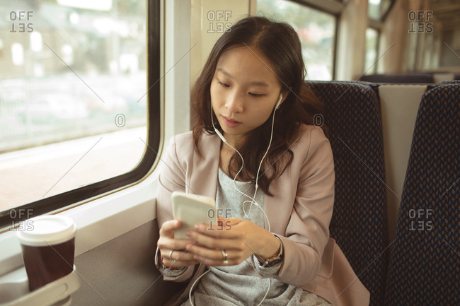 Woman using mobile phone while listening music on mobile phone in train