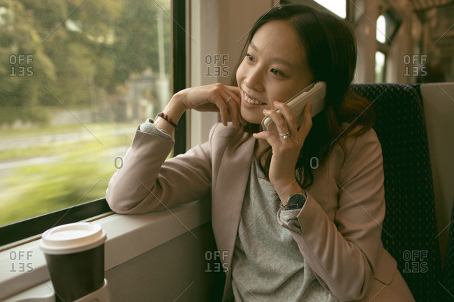 Happy woman talking on mobile phone while travelling in train