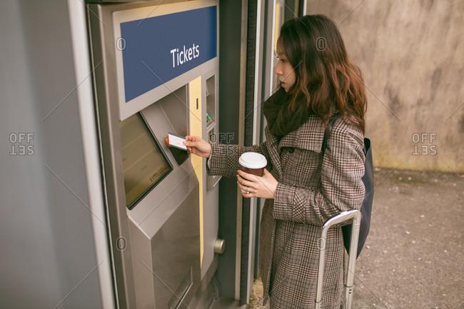 Woman taking ticket from machine at railway platform