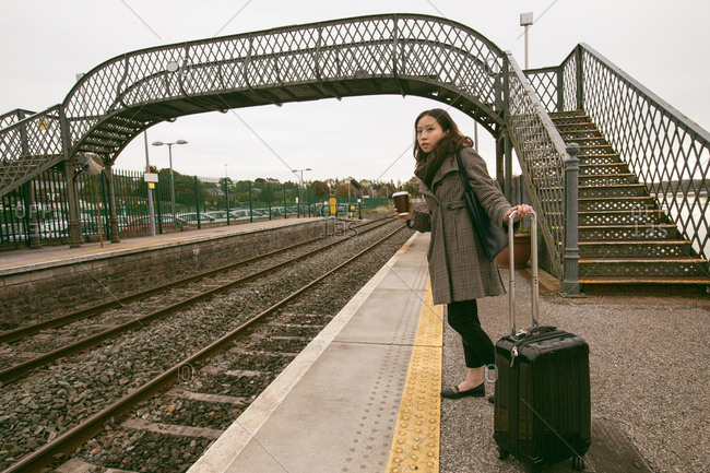Woman waiting for the train with luggage at railway platform