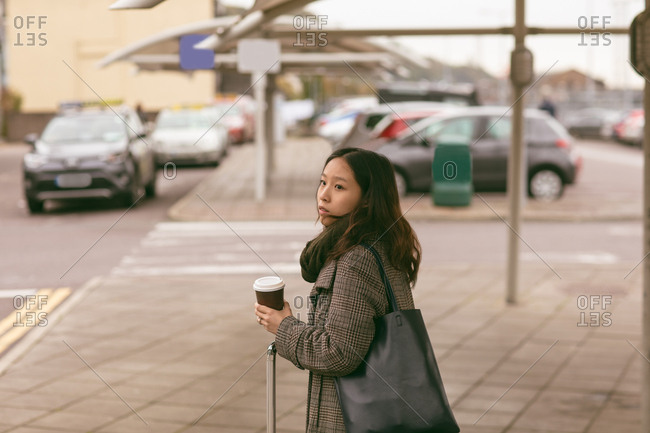 Beautiful woman with luggage standing at taxi stand