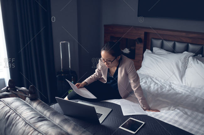 Woman reading document while working on laptop in hotel
