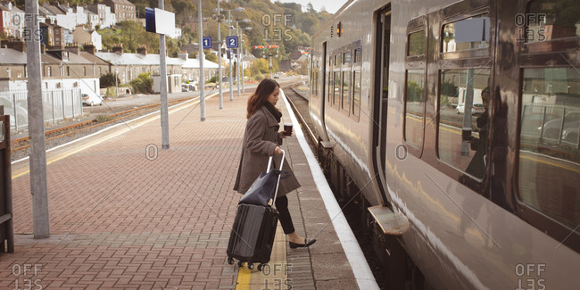 Woman getting in the train with luggage at railway platform