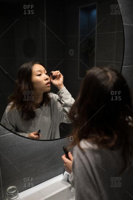Beautiful woman applying mascara in front of mirror
