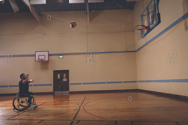 Side view of disabled man practicing basketball in the court