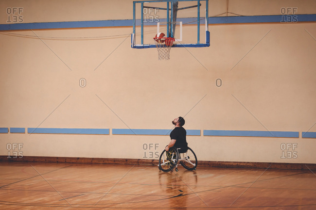 Disabled man practicing basketball alone in the court