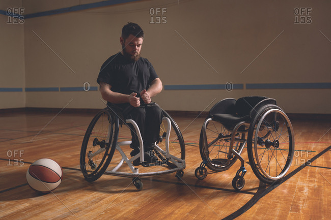 Disabled man adjusting belt of wheelchair in the court