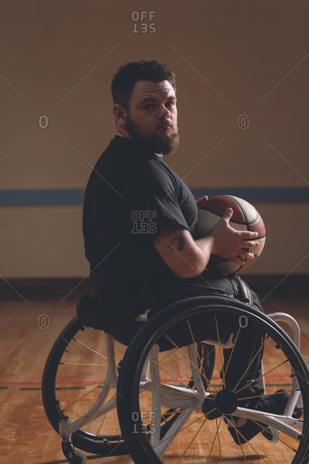 Portrait of disabled man holding basketball in the court