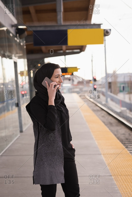 Woman in hijab talking on mobile phone at railway station