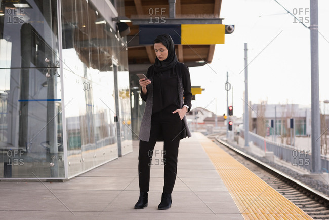 Woman in hijab using mobile phone at railway station