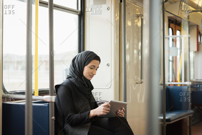 Woman in hijab using digital tablet while travelling in train