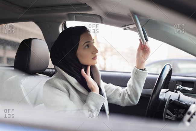Young woman in hijab looking at rear-view mirror