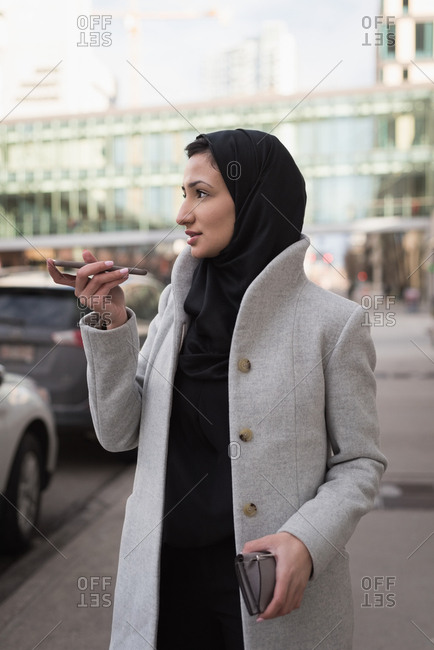 Woman in hijab talking on mobile phone at city street