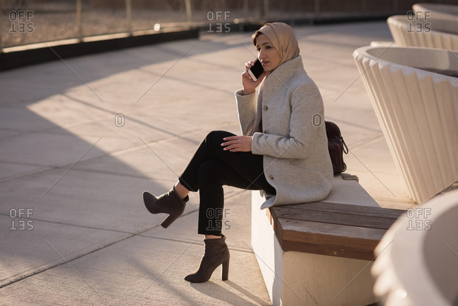 Woman in hijab talking on mobile phone on a sunny day