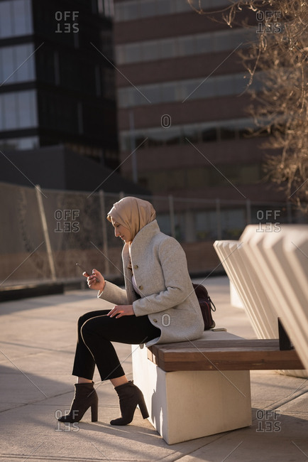 Woman in hijab using mobile phone on a sunny day